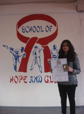 Karishma with black belt and certificate.